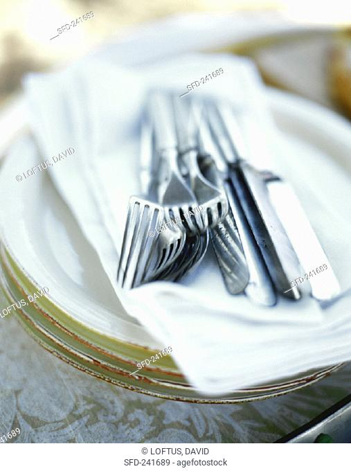 Knives and forks on napkin on pile of plates