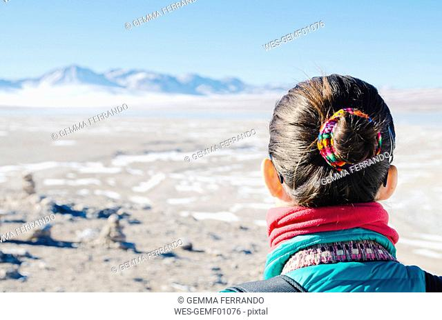 Bolivia, Woman with a bun made with native canvas looking the landscape