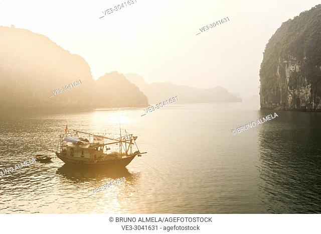 Sunrise over fishing boat in the karst landscape of Ha Long Bay, Quang Ninh Province, Vietnam. Ha Long Bay is a UNESCO World Heritage Site