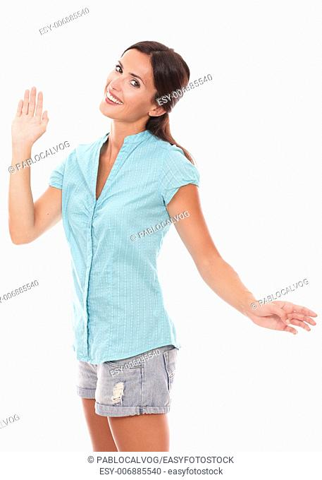 Lovely young woman gesturing a greeting while looking at you standing and smiling in white background