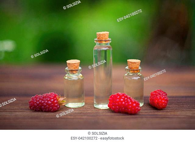 Essence of Wild raspberries on a table in a beautiful glass Bottle