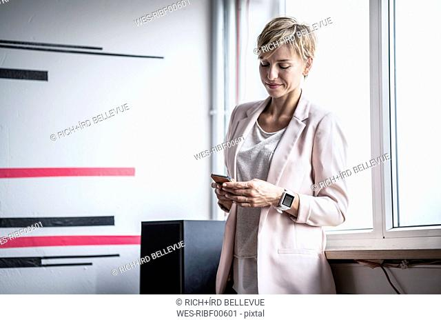 Businesswoman at the window looking at cell phone