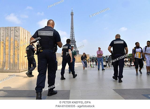 Security personnel walk near the fence of a construction site at the Palais du Trocadero in front of the Eiffel tower in Paris, June 8, 2016