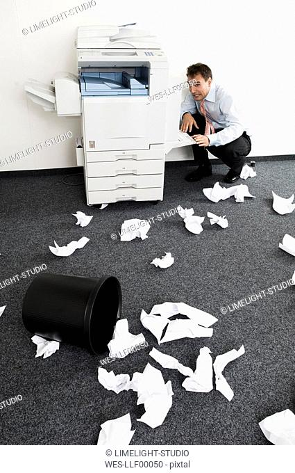 Businessman squatting in despair next to copying machine