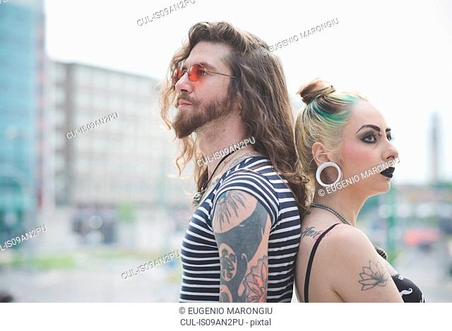 Portrait of punk hippy couple back to back on city street