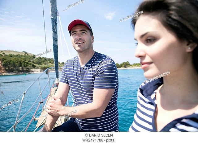 Happy couple on bow of sailboat
