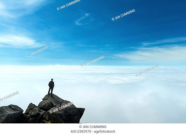 A hiker admiring the view from the top of Sgurr nan Eag, one of the peaks in the Black Cuillin; Isle of Skye, Scotland