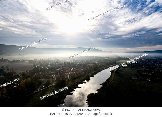 16 October 2018, Lower Saxony, Hemeln: Fog can be seen over the Weser, which separates the states of Lower Saxony and Hesse between Hemeln (left) and...