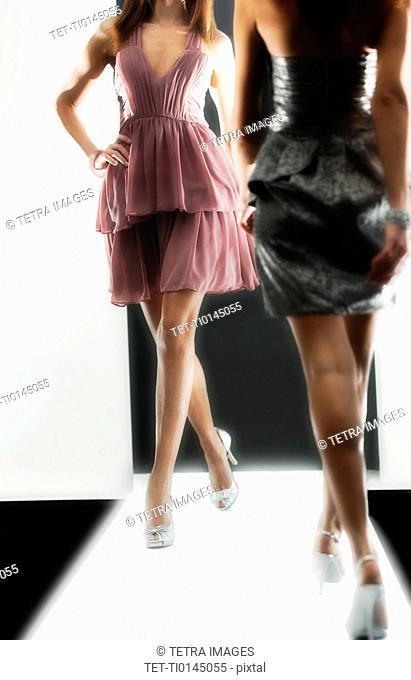 Two female fashion models wearing dresses on catwalk