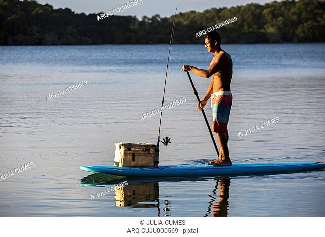 Young Man With His Fishing Gear On A Stand Up Paddle Board