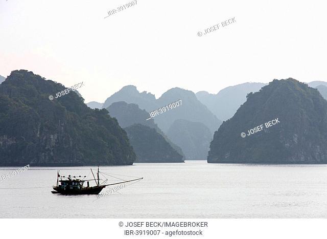 Fishing boat in front of limestone cliffs in Halong Bay, Gulf of Tonkin, North Vietnam, Vietnam