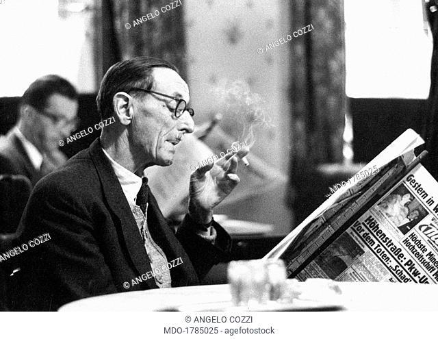 Man reading a newspaper at Cafe Demel. A man relaxing reading a newspaper at Cafe Demel. Vienna, 1960s