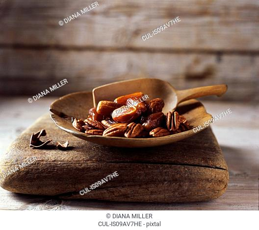 Dates and walnuts in rustic wooden bowl with wooden scoop
