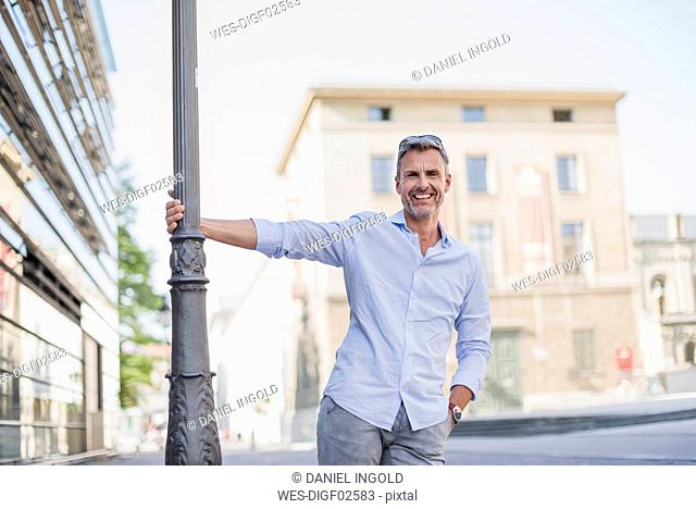 Portrait of happy man at lamp pole in the city