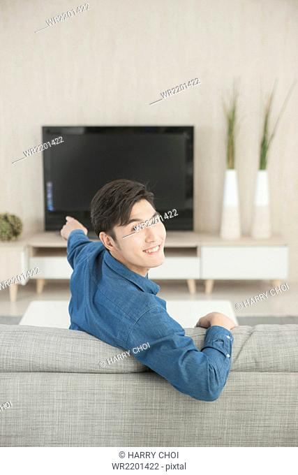 Portrait of young man looking back holding a TV remote control