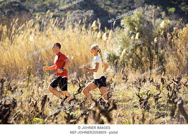 Young couple running through field