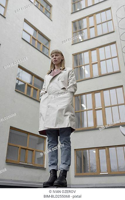 Caucasian woman wearing a coat near building