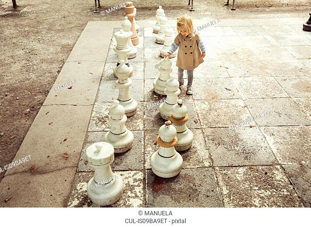 Female toddler playing with giant chess in park