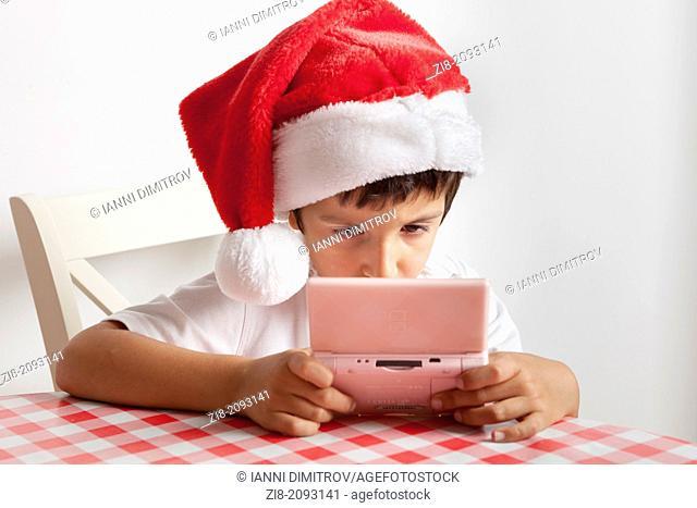 Boy in Santas hat plays computer game