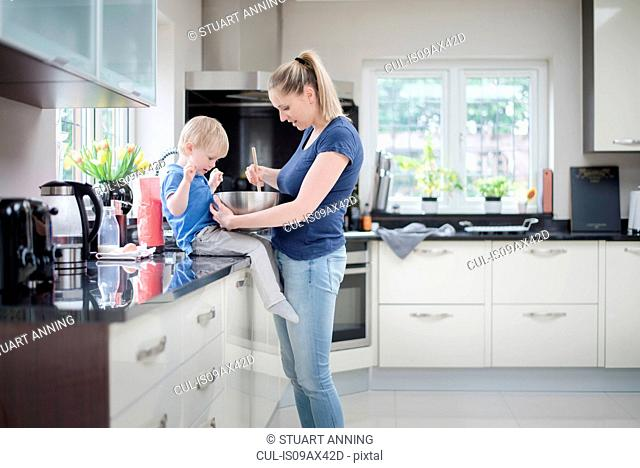Mother and son baking together, stirring mixture in mixing bowl