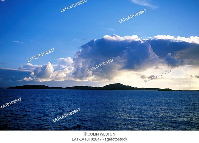 Western Isles. View of islands offshore at sunset. Silhouettes. Line of low cloud