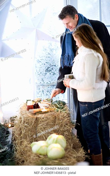 Man and woman looking at produce on hay bale in greenhouse