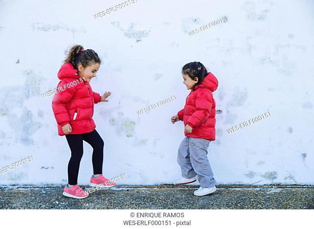 Two little girls dancing in front of a wall