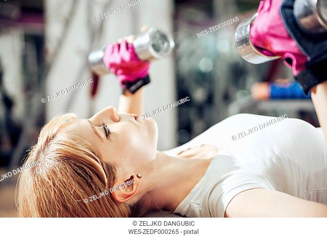 Pregnant woman doing exercises with hand handles in gym