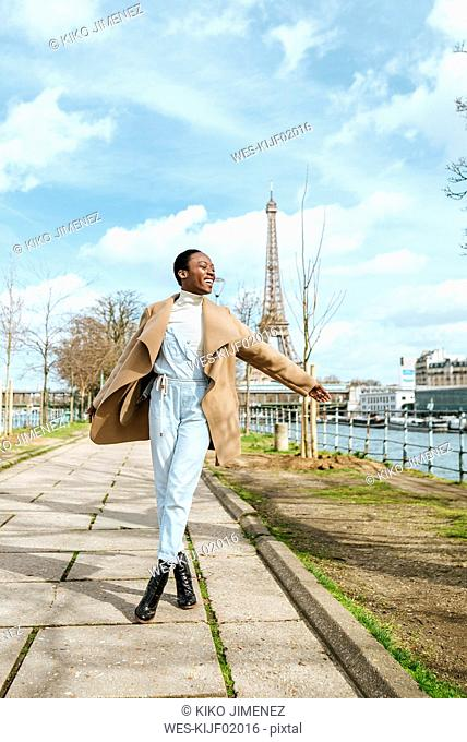 France, Paris, Happy woman walking at the riverside with the Eiffel tower in the background