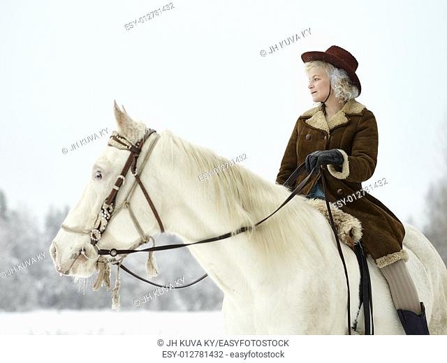 Attractive woman wearing winter jacket and hat, she riding a white horse. South Finland in February