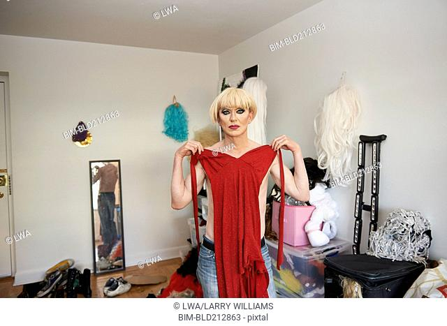 Caucasian drag queen choosing gown in living room