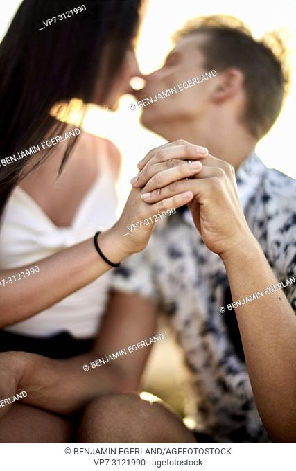 Sensual couple kissing while touching fingers, love, emotions, relationship, dating. Chersonissos, Crete, Greece