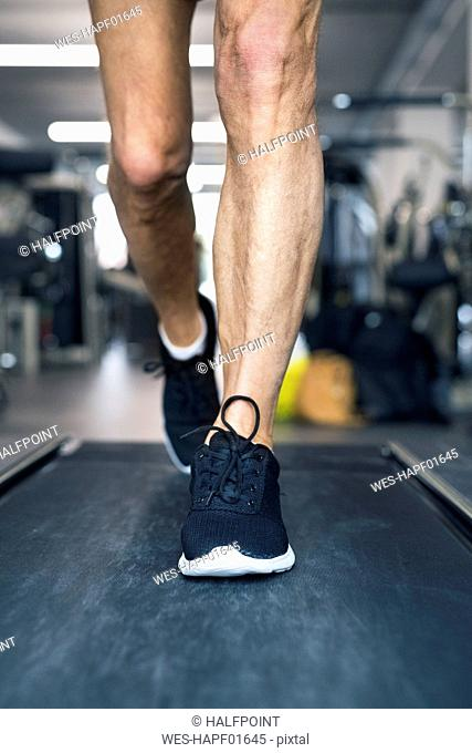 Legs of man on treadmills working out in gym