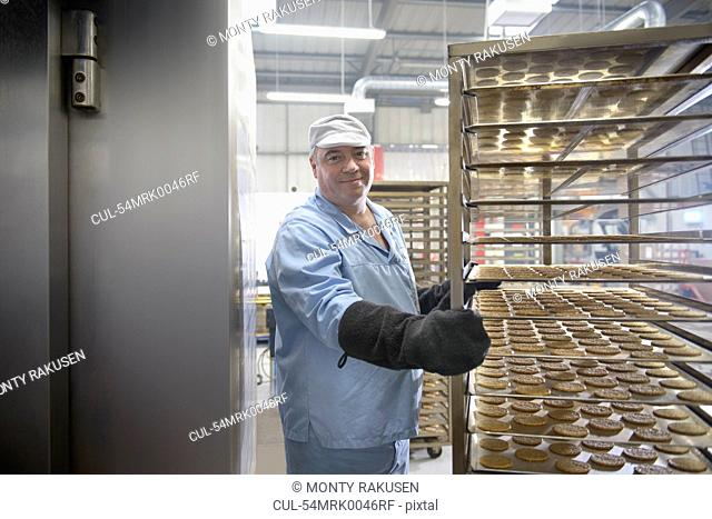Worker baking biscuits in factory