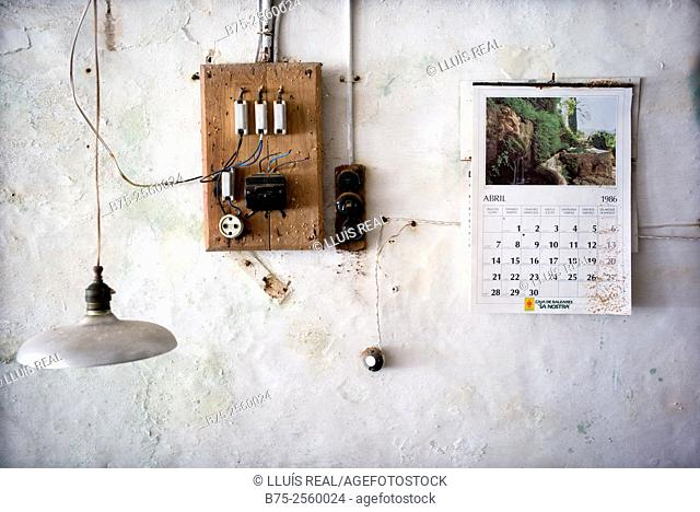 Wall of an old workshop with an electrical fuse box and plug. A calendar from April 1986 on the wall, and a lamp hanging from the ceiling