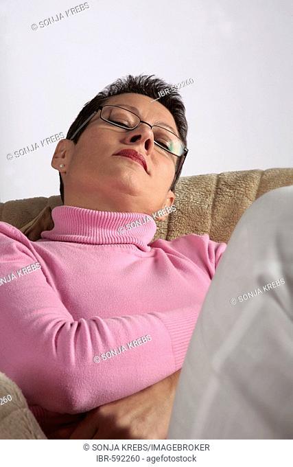 Woman napping comfortably on sofa