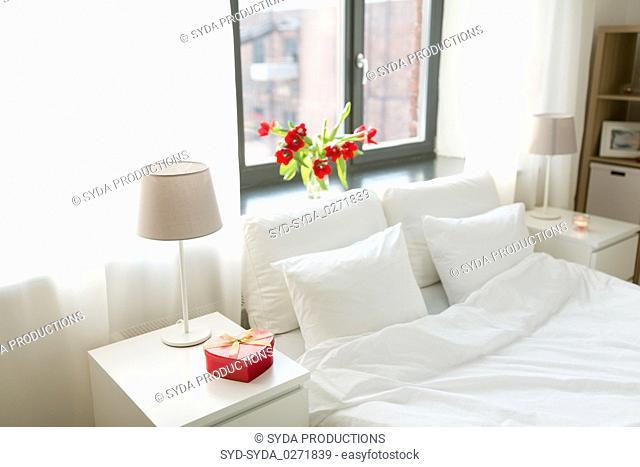 gift in shape of heart on bedside table in bedroom