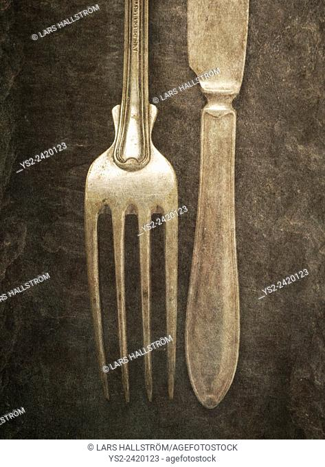 Still life with silverware on table. Knife and fork on a stone background