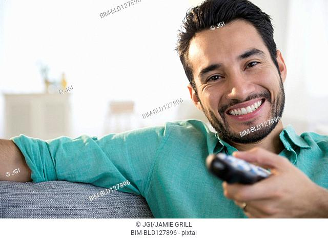 Mixed race man watching TV on sofa