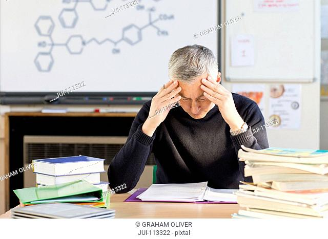 Stressed science teacher trying to grade homework in classroom