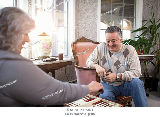 Mature couple at home playing backgammon