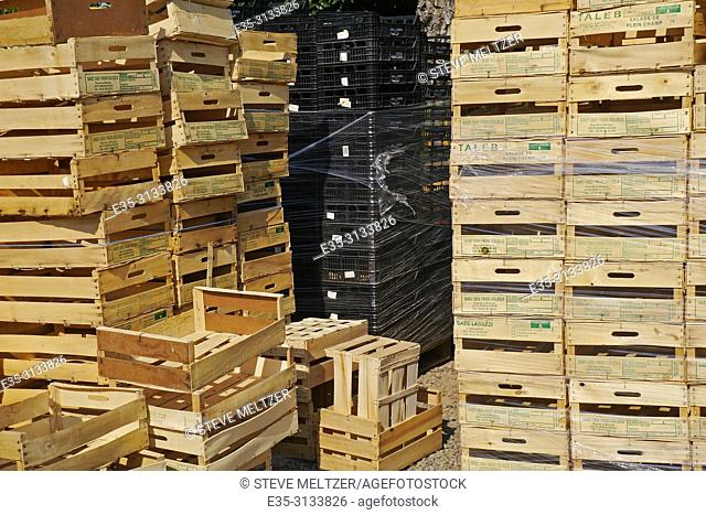 Stacks of wooden fruit and vegetable crates at a fruit stand