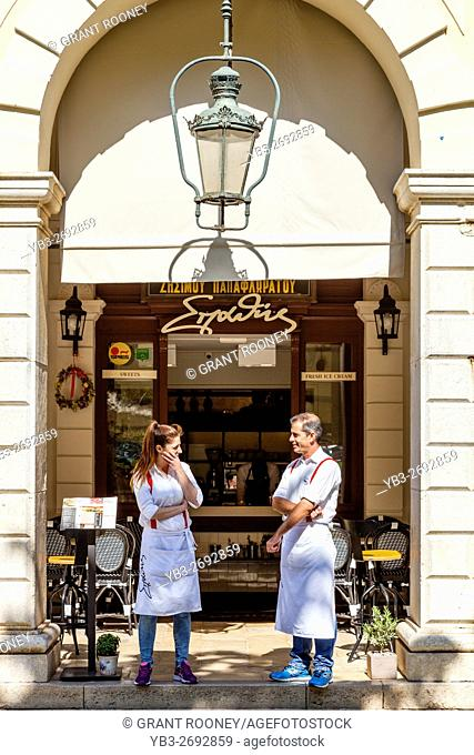 A Waiter and Waitress Wait For Customers At A Cafe In The Fashionable Liston Area, Corfu Old Town, Corfu, Greece