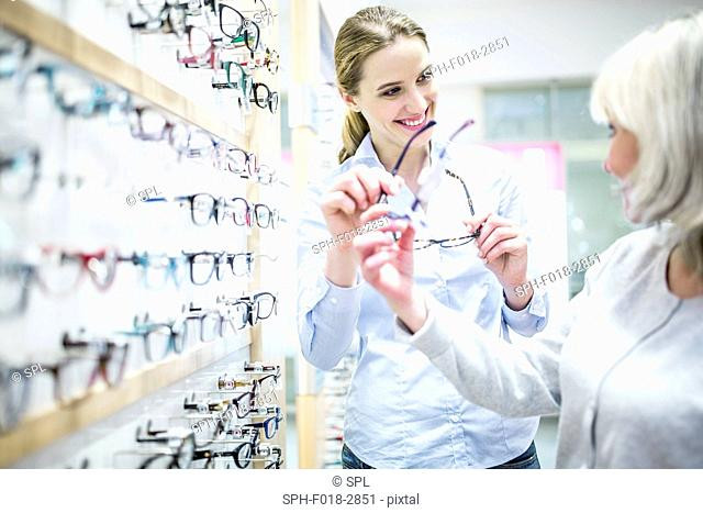 Smiling optometrist helping patient shopping for new spectacles