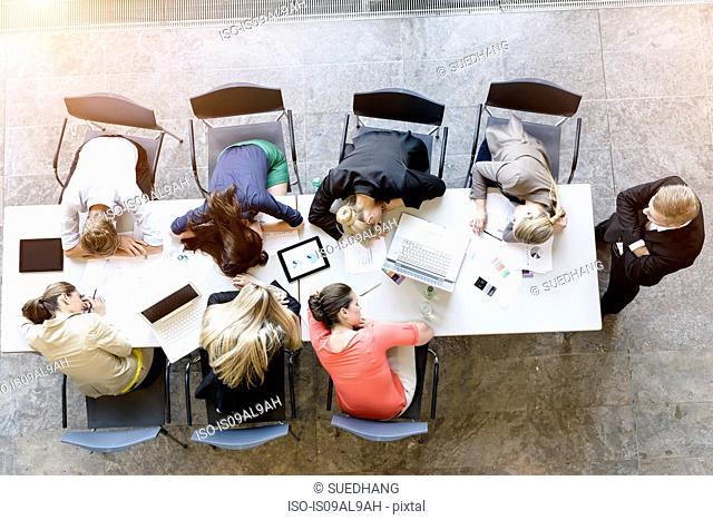 Overhead view of exhausted business team leaning on desk in office