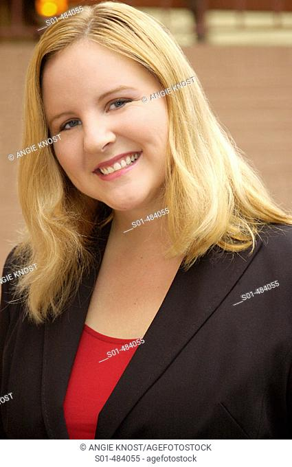 Headshot of young professional blond woman in her mid twenties 20's.  She is wearing a black suit jacket and red shirt, smiling and making eye contact with...