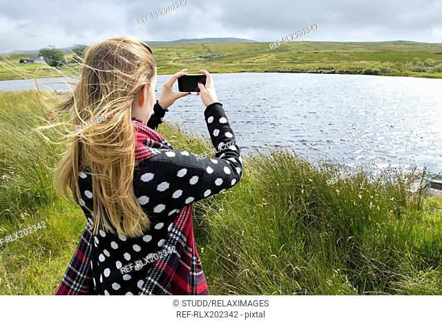 Rear view of teenage girl photographing lake through smart phone