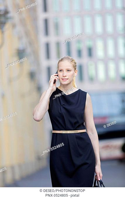 Pretty business woman with bag and talking on the phone, walking in downtown