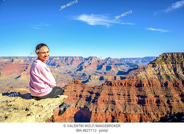 Young smiling woman, sitting at the abyss of the gigantic gorge of the Grand Canyon, view from the Rim Trail, between Mather Point and Yavapai Point