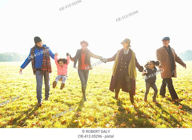 Playful multi-generation family walking in sunny autumn park grass